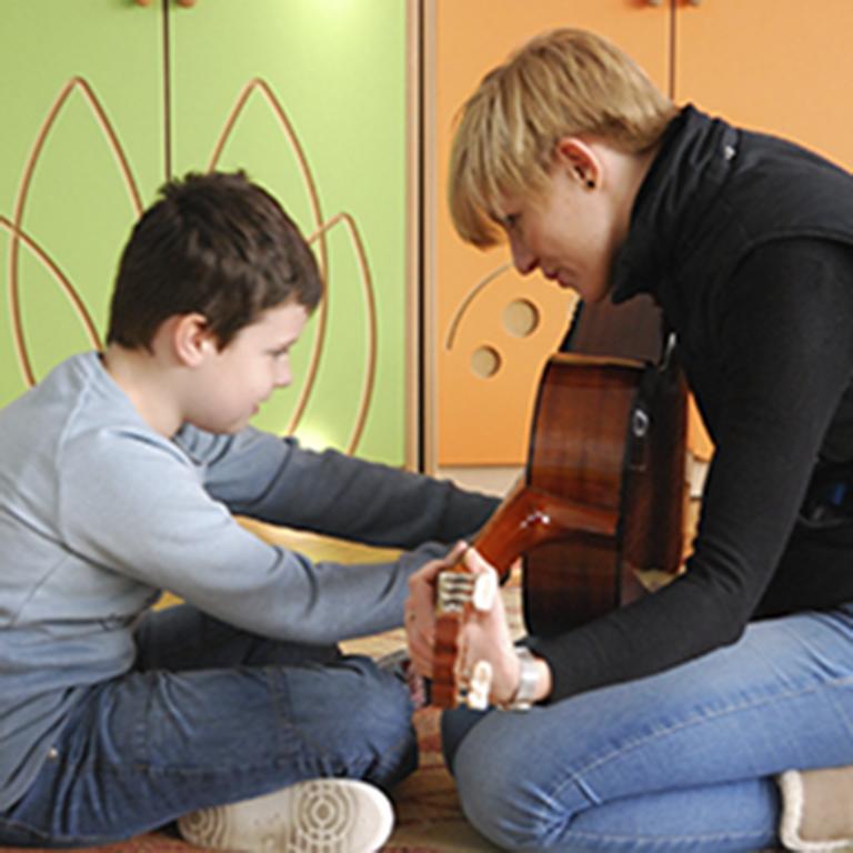 Dziecko gra na gitarze razem z muzikoterapeutą Sarą Knapik-Szweda